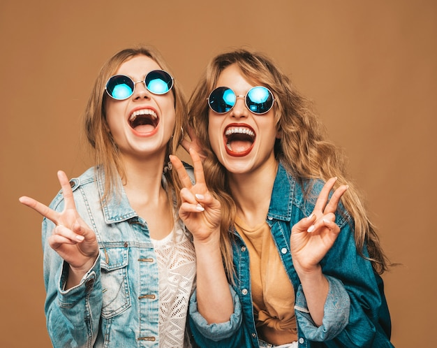 トレンディな夏服とサングラスで2人の若い美しい笑顔の女の子。セクシーな屈託のない女性がポーズします。ポジティブな叫びモデル