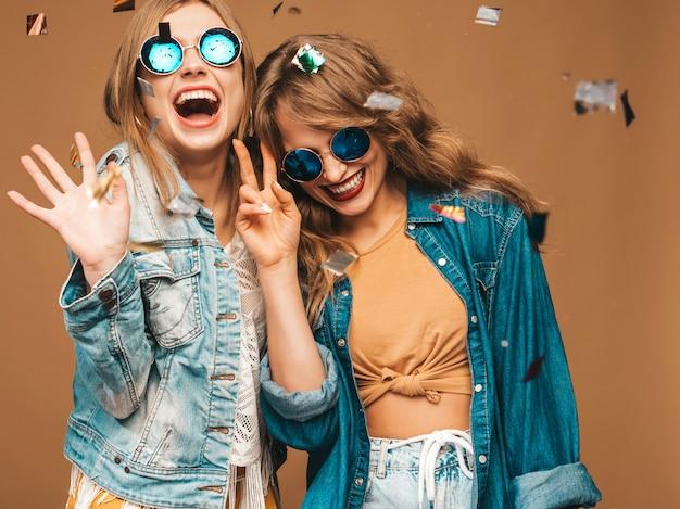 トレンディな夏服とサングラスで2人の若い美しい笑顔の女の子。セクシーな屈託のない女性がポーズします。紙吹雪の下で肯定的な悲鳴モデル