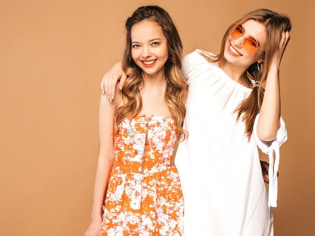 トレンディな夏服の2人の若い美しい笑顔の女の子。セクシーな屈託のない女性がポーズします。ラウンドサングラスのポジティブモデル