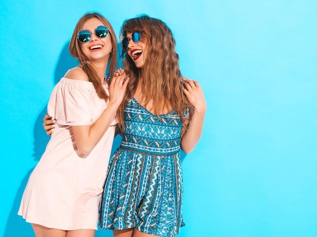 トレンディな夏のドレスとサングラスの2人の若い美しい笑顔の女の子。セクシーな屈託のない女性がポーズします。ポジティブモデル