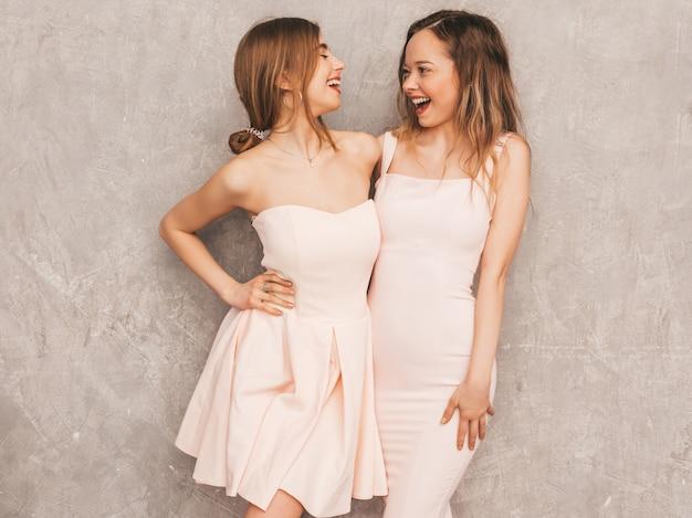 トレンディな夏の2人の若い美しい笑顔の女の子は、ピンクのドレスを光します。セクシーな屈託のない女性がポーズします。楽しいポジティブモデル