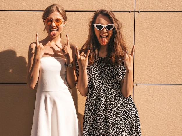 トレンディな夏の2人の若い美しい笑顔流行に敏感な女の子をドレスアップします。