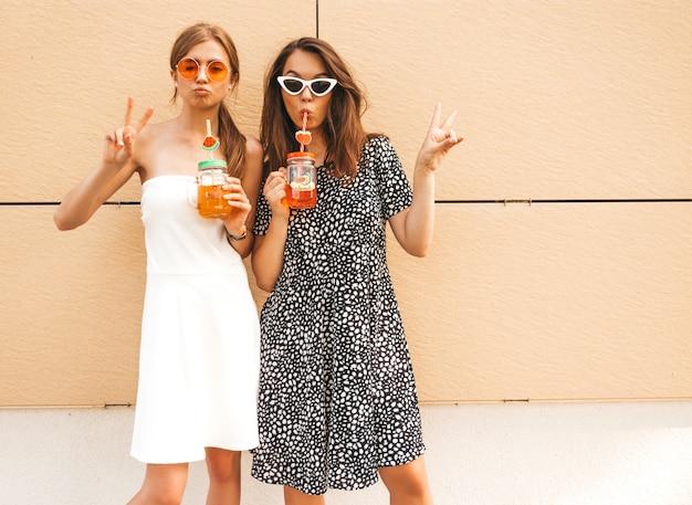 トレンディな夏のドレスの2人の若い美しい笑顔流行に敏感な女の子。