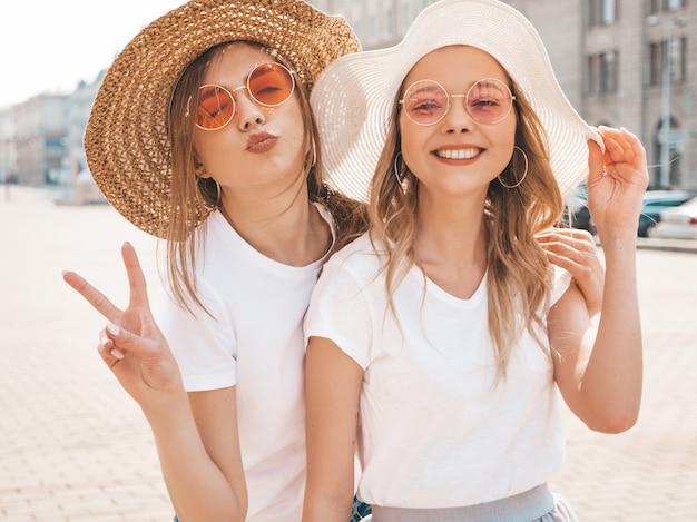 トレンディな夏服で流行に敏感な女の子を笑顔2つの若い美しいブロンド。ピースサインを表示