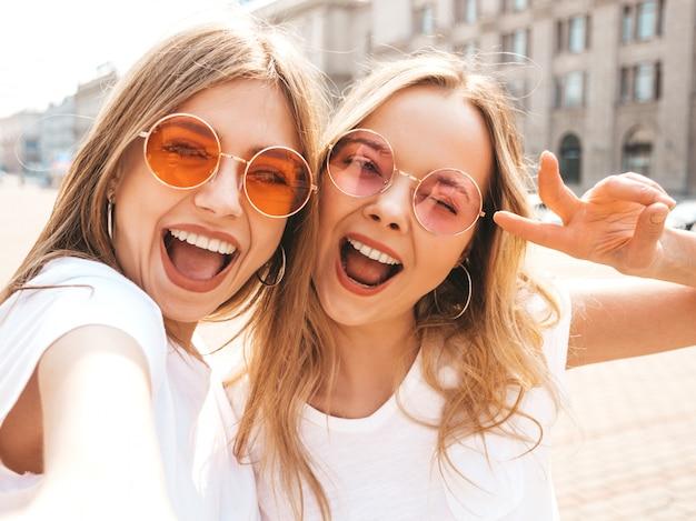 2 молодых усмехаясь женщины битника белокурых в одеждах футболки лета белых.