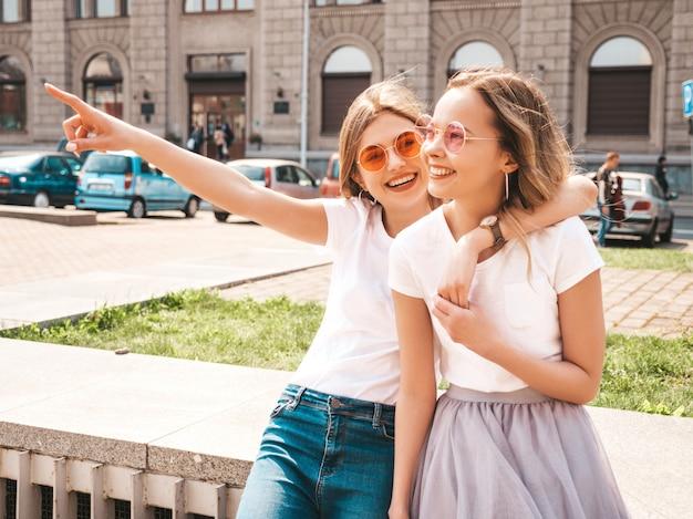 白い流行に敏感な服のポーズで夏の晴れた日に2つの若いスタイリッシュなヒッピーブルネットとブロンドの女性モデルのファッションの肖像画