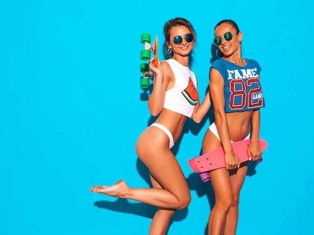 夏のパンツとトピックの2人の美しい笑顔のセクシーな女性。サングラスのトレンディな女の子。カラフルなペニースケートボードを楽しんでいるポジティブなモデル。孤立した