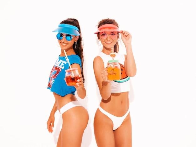 白い夏のパンツとトピックの2人の美しい笑顔のセクシーな女性。サングラス、透明なバイザーキャップのトレンディな女の子。発狂。面白いモデルが分離されました。新鮮なカクテルスムージードリンクを飲む