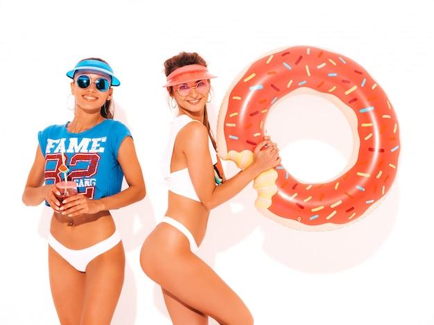白い夏のパンツとトピックの2人の美しい笑顔のセクシーな女性。サングラスの女の子、透明なバイザーキャップ。ドーナツリロインフレータブルマットレスと新鮮なカクテルスムージードリンクを飲むモデル