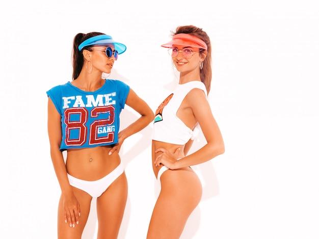 白い夏のパンツとトピックの2人の美しい笑顔のセクシーな女性。サングラスと透明なバイザーキャップの女の子。楽しいトレンディなモデル。白で隔離
