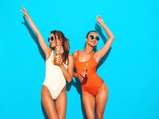 夏のカラフルな水着水着で2人の美しいセクシーな笑顔の女性。サングラスのトレンディな女の子。発狂。面白いモデルが分離されました。新鮮なカクテルスムージードリンクを飲みます。手を上げる