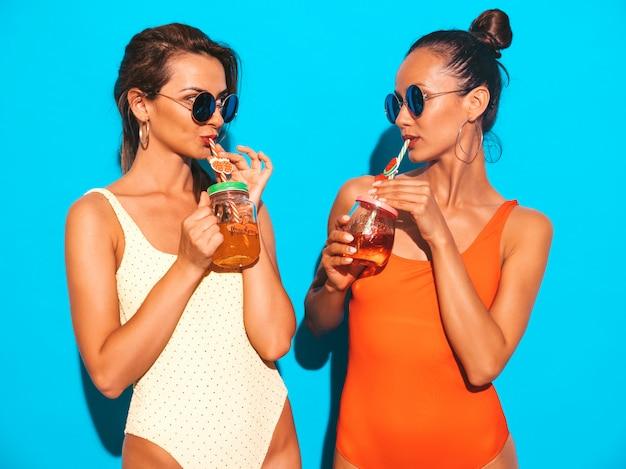 夏のカラフルな水着水着で2人の美しいセクシーな笑顔の女性。サングラスのトレンディな女の子。発狂。面白いモデルが分離されました。新鮮なカクテルスムージードリンクを飲む