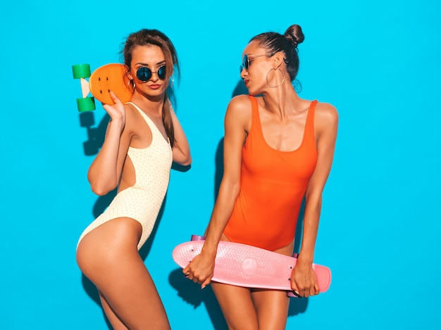 夏のカラフルな水着水着で2人の美しいセクシーな笑顔の女性。サングラスのトレンディな女の子。カラフルなペニースケートボードを楽しんでいるポジティブなモデル。孤立した