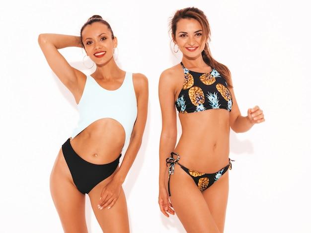 水泳ランジェリーで2人の美しいセクシーな笑顔の女性。楽しいトレンディなホットモデル。分離された女の子