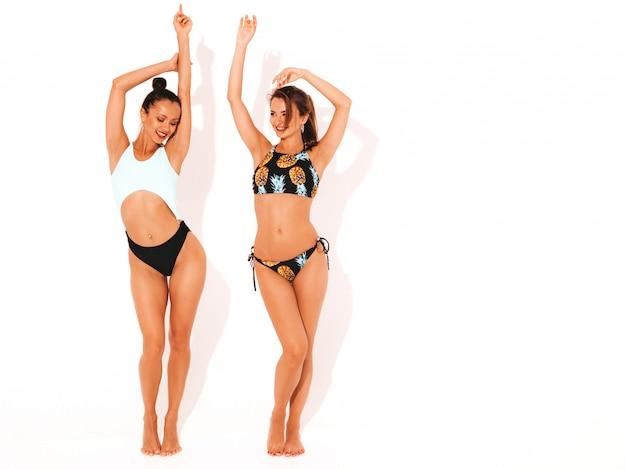 水泳ランジェリーで2人の美しいセクシーな笑顔の女性。楽しいトレンディなホットモデル。分離された女の子。完全な長さの手を上げる