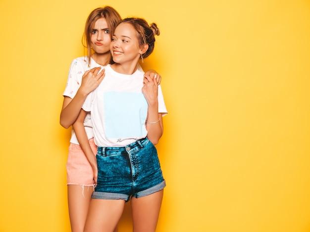 トレンディな夏服で2人の若い美しい笑顔流行に敏感な女の子。黄色の壁に近いポーズセクシーな屈託のない女性。ポジティブなモデルが夢中になって楽しんでいます。