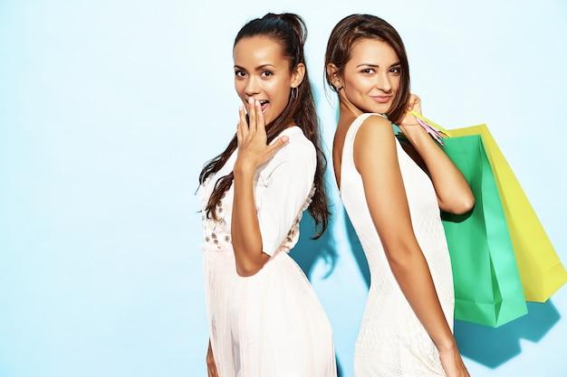 買い物袋を保持している2人の若いセクシーなスタイリッシュな笑顔ブルネット女性の肖像画。夏の流行に敏感な服を着た熱い女性。青い壁を越えてポーズポジティブモデル