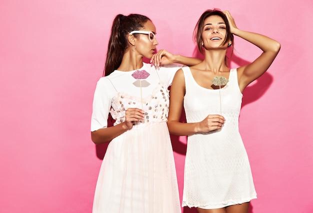 紙コップとスティックに大きな唇の2人の面白い女性。スマートと美容のコンセプト。パーティーの準備ができてうれしそうな若いモデル。ピンクの壁に分離された女性。ポジティブな女性