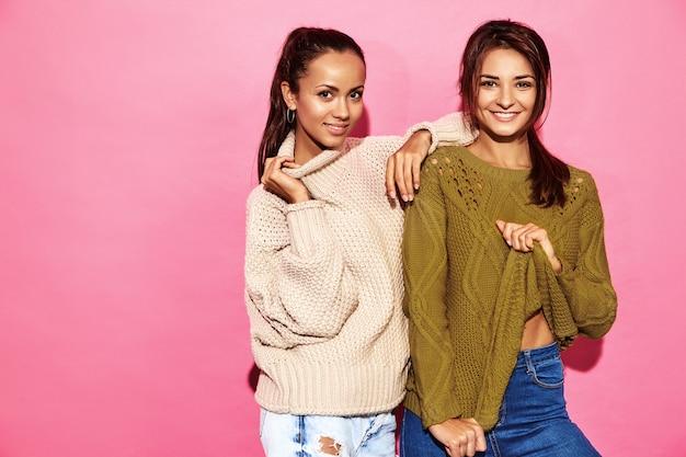 2人の美しい笑顔の豪華な女性。ピンクの壁にスタイリッシュな白と緑のセーターで立っている女性。