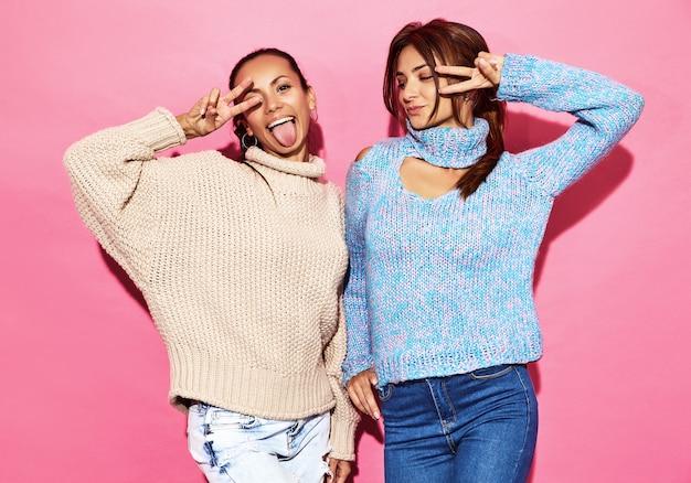 2人の美しい笑顔の豪華な女性。青い壁にスタイリッシュな白と青のセーターで立っている女性。