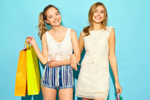 買い物袋を保持している2人の若いスタイリッシュな笑顔金髪女性の肖像画。夏の流行に敏感な服を着た女性。青い背景の上にポーズをとってポジティブモデル