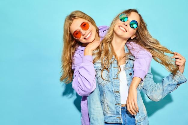 トレンディな夏服で流行に敏感な女性を笑顔2人の若い美しいブロンド。サングラスの青い壁に近いポーズセクシーな屈託のない女性。夢中になってハグするポジティブなモデル