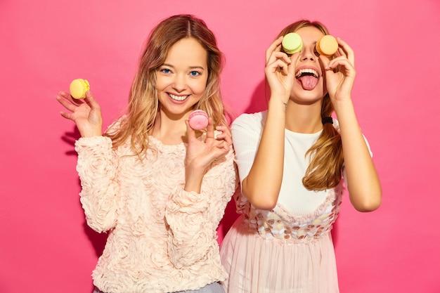 トレンディな夏服の2人の若い魅力的な美しい笑顔流行に敏感な女性。メガネ、カラフルなマカロンの眼鏡、目の場所にマカロンを保持している女性。ピンクの壁でポーズ