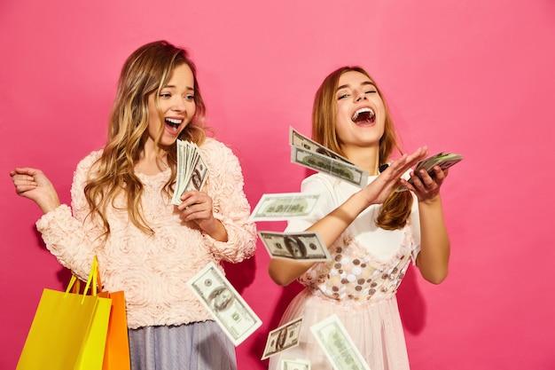 買い物袋を保持している2人の若いスタイリッシュな笑顔金髪女性の肖像画。夏の流行に敏感な服を着た女性。ピンクの壁にお金をかける肯定的なモデル