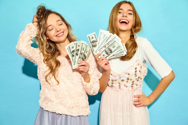 勝利を喜ぶ夏の服を着て、青い壁に分離された現金お金を保持している2人の幸せな喜んでブロンド女性の肖像画
