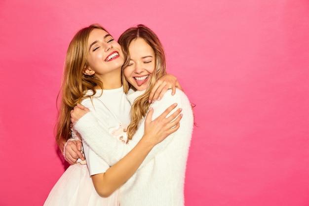 トレンディな夏の白い服の2人の若い美しい笑顔流行に敏感な女性。セクシーな屈託のない女性が青い壁の近くでポーズします。抱き締めるポジティブモデル