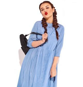 夏のカラフルな青いドレスと分離されたバックパックの手で明るい化粧品で若い幸せな笑顔の女性モデルと2つのおさげの赤い唇の肖像画。空気キスを与える