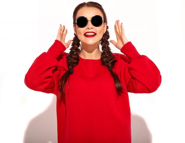 Портрет молодой счастливой усмехаясь модели женщины с ярким составом и красочных губ с 2 отрезками провода и солнечных очков в изолированных одеждах лета красных.