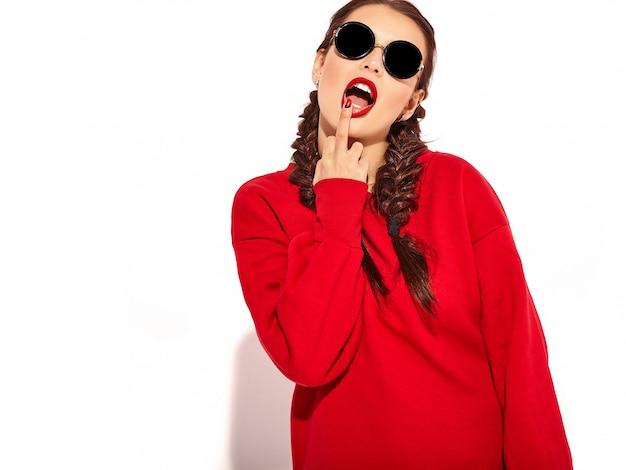 明るいメイクと2つのおさげ髪と分離された夏の赤い服のサングラスとカラフルな唇を持つ若い幸せな笑顔の女性モデルの肖像画。中指をなめる、サインオフファック