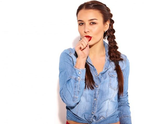 分離された夏のブルージーンズの服で明るいメイクと2つのおさげの赤い唇の若い幸せな笑顔の女性モデルの肖像画。噛む指