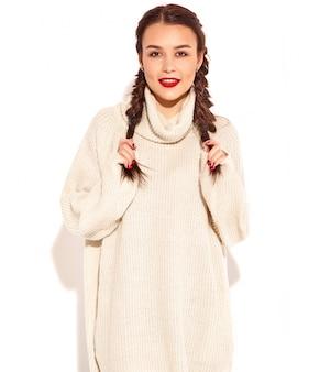 明るい化粧と若い幸せな笑みを浮かべて女性モデルの肖像画と分離された夏暖かいセーター服で2つのおさげ髪と赤い唇。