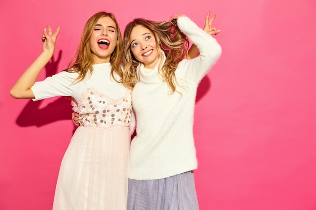 トレンディな夏の白い服の2人の若い美しい笑顔の女性