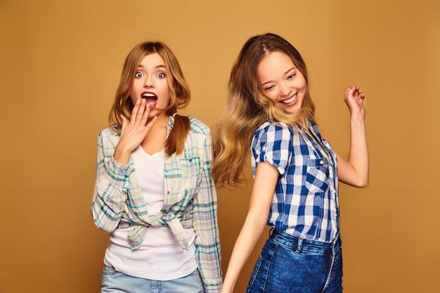 トレンディな夏の格子縞のシャツに笑みを浮かべて2つの若い美しいブロンド