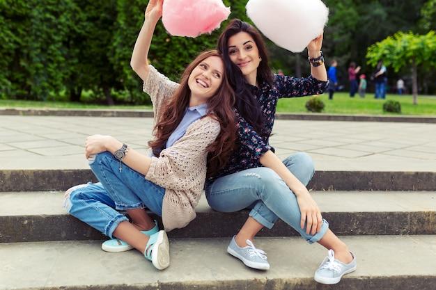 屋外の綿菓子を楽しんで2人の陽気な女の子