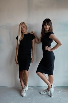 屋内の黒のドレスで2つのきれいな女性