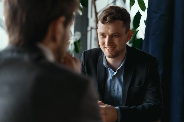 何かを議論する2人の若いビジネスマン