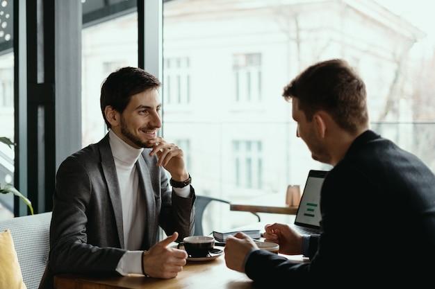 レストランで成功した会議を持つ2つの青年実業家。