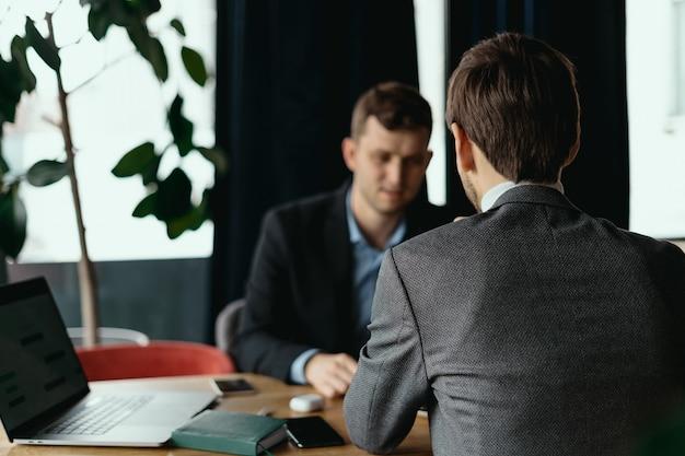 カフェでの会議中にラップトップで働く2人の男性