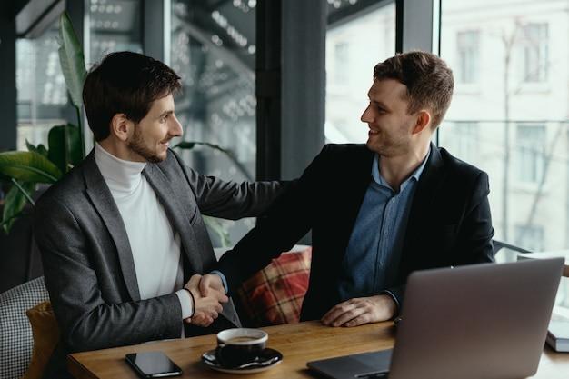 ロビーで会議中に握手する2人のビジネスマン