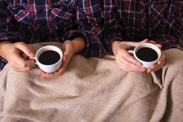 男性と女性の手がワームチェック柄のコーヒー2杯を保ちます。
