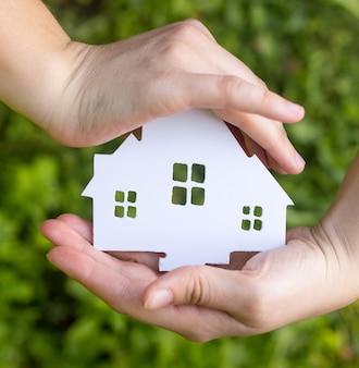 新鮮な緑の芝生の上の小さな紙の家族の家の切り欠きを保持している2つの女性の手。
