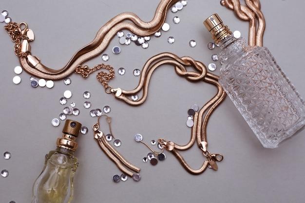 灰色の背景の金のジュエリーアクセサリーと香水の2つのボトル