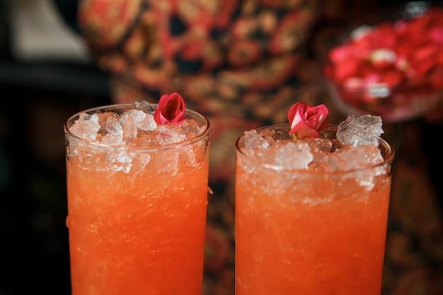 プロのバーテンダーが2つの赤いカクテルを作り、生花でそれらを飾ります。バーではカクテルを楽しめます。