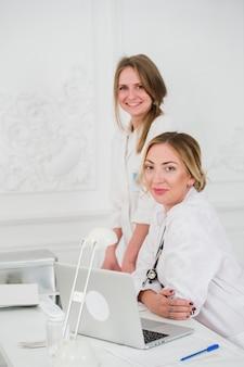 2つの女性のフレンドリーな陽気な医師や看護師分離オフィス笑顔で