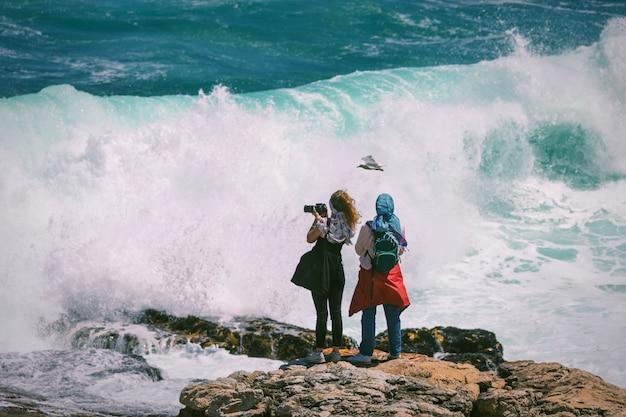 南アフリカのヘルマナスで巨大な危険な波とその上を飛んでいるカモメに直面して写真を撮る2人の若い女性観光客