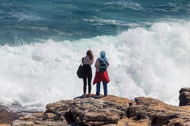 南アフリカのヘルマナスで巨大な危険な波に直面して写真を撮る2人の若い女性観光客